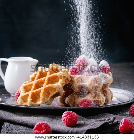 Belgian waffles with raspberries and sieving sugar powder, served with jug of milk on vintage metal tray with textile napkin over old wooden table. Dark rustic style. Square image - stock photo