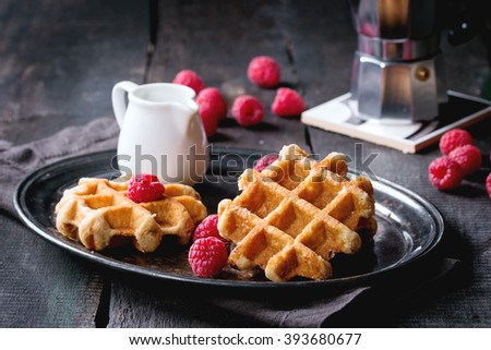Belgian waffles with raspberries, served with coffee pot and jug of milk on vintage tray over old wooden table. - stock photo
