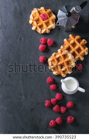 Belgian waffles with raspberries, served with coffee pot and jug of milk over black stone slate background. Flat lay - stock photo