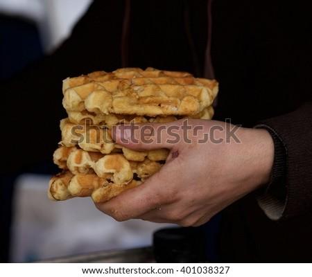 Belgium waffle, belgium food, typical belgium sweet, fragment photo, man holding belgium waffle in his hand with blurry dark background  - stock photo