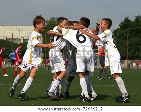 BELGOROD, RUSSIA - AUGUST 04: Unidentified boys embraces after goal on August, 04 2010 in Belgorod, Russia. The final of Chernozemje superiority, Football kinder team of 1996 year of birth. - stock photo