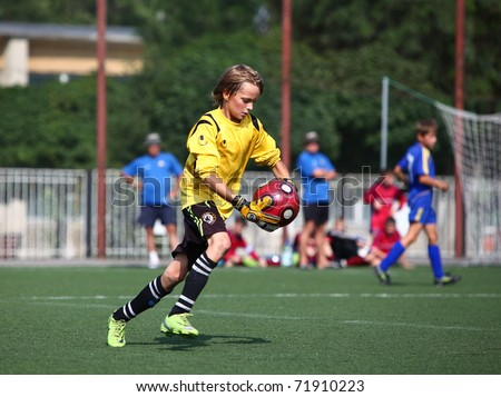 BELGOROD, RUSSIA - JULY 4: Unidentified boys plays football as goalkeeper July, 4 2010 in Belgorod, Russia. The final of Chernozemje superiority, Football kinder team of 1998 year of birth. - stock photo