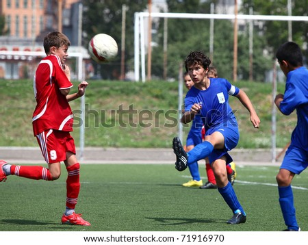BELGOROD, RUSSIA - JULY 07: Unidentified boys plays football on July, 07 2010 in Belgorod, Russia. The final of Chernozemje superiority, Football kinder team of 1996 year of birth. - stock photo
