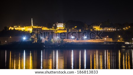 Belgrade fortress Kalemegdan and the monument of Victor in the night time with the port on river Sava below with reflecting lights in the river - stock photo