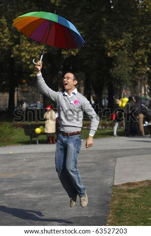 """BELGRADE - OCTOBER 10: Young gay is jumping during """"Belgrade Pride Parade"""" October 10, 2010 in Belgrade, Serbia. - stock photo"""