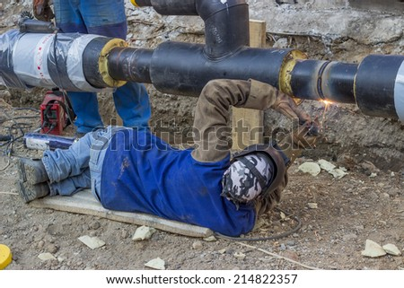 BELGRADE, SERBIA - AUGUST 14: Welder welding underground steel pipe lying on ground. Pipe is supported by crane. Pipe is tack welded. Selective focus. At street Vojvode Stepe in August 2014. - stock photo