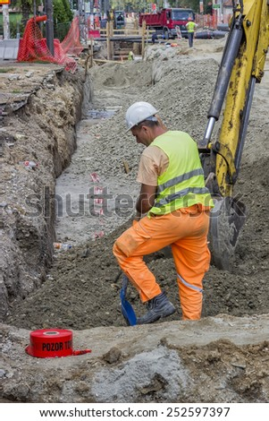 BELGRADE, SERBIA - AUGUST 09: Worker and excavator bucket backfilling trench for the ground piping. At construction site in August 2014. - stock photo