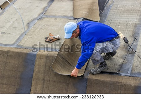 BELGRADE, SERBIA - NOVEMBER 11: Insulation worker and propane blowtorch at floor slab waterproofing works. Worker heating and melting bitumen felt. At construction site in November 2014. - stock photo