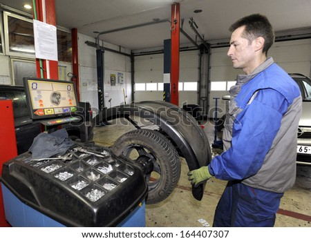 BELGRADE, SERBIA - NOVEMBER 25, 2013: Workers changes tires in car mechanic shop on November 25, 2013 in Belgrade - stock photo