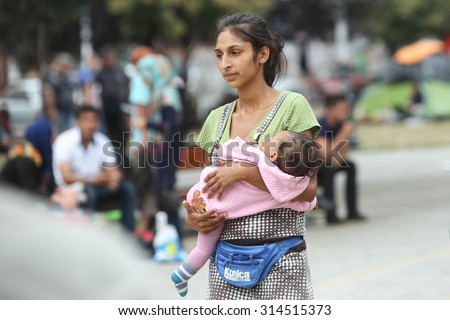 BELGRADE, SERBIA - SEPTEMBER 5 : A young Syrian woman holding a child in a park near the train station, waiting for the transport to the European Union on September 5th, 2015 in Belgrade, Serbia.  - stock photo