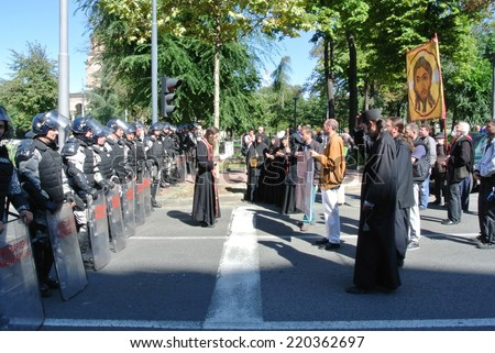 BELGRADE, SERBIA - SEPTEMBER 28, 2014: Strong police forces safeguard the perimeter of the gay pride, while members of the clergy protest against the pride in front of a police cordon. - stock photo