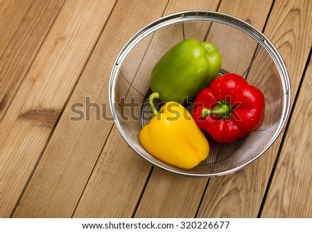 Bell peppers on a wooden table in a culllender - stock photo