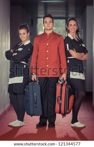 Bellboy with Two Beautiful Chambermaids - stock photo