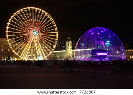 Bellecour square  with its equestrian statue of Louis XIV under a snowglobe and the ferris - stock photo