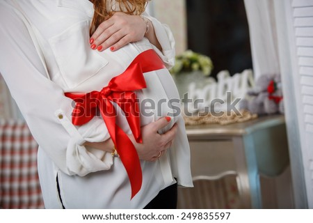 belly of a pregnant woman tied with a red ribbon   tum and red bow   Pregnant woman embracing her soft tummy - stock photo