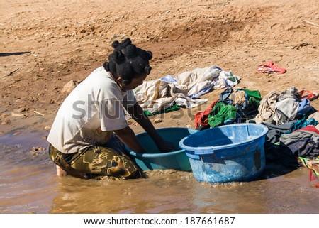 BELO SUR TSIRIBIHINA, MADAGASCAR, JUL 3:  Unidentified woman washnig  clothes on jul 3, 2006 in the Tsiribihina river, western Madagascar - stock photo