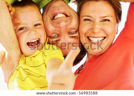 Below angle of cheerful couple looking at camera while on summer vacation - stock photo