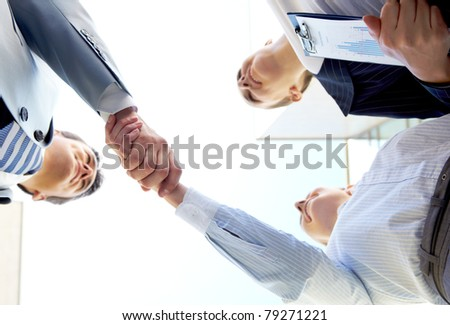 Below angle of successful associates handshaking after striking deal - stock photo