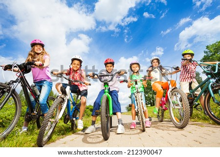 Below angle view of kids in helmets with bikes - stock photo