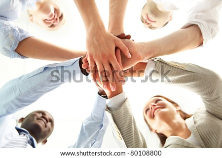 Below shot of smiling co-workers making pile of hands and looking at each other - stock photo