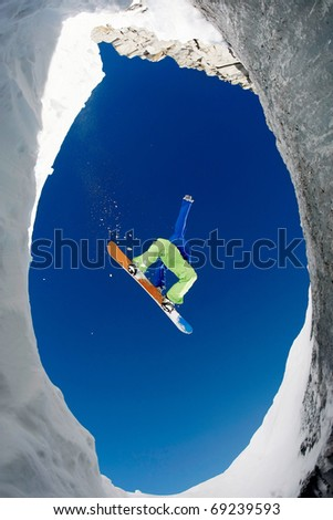 Below view of extreme snowboarder surrounded by rocky mounts covered with snow - stock photo
