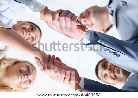Below view of four people handshaking - stock photo