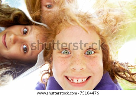 Below view of happy girl with funny expression staring at you - stock photo