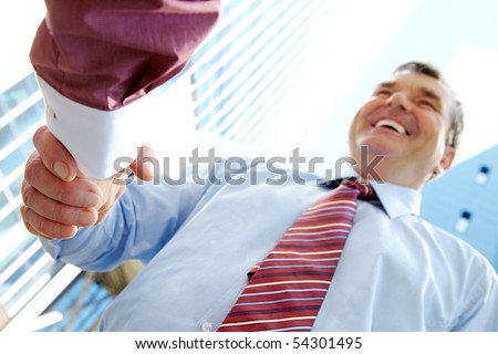 Below view of happy senior chief handshaking outdoors with partner at background of modern building - stock photo