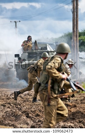BELTRING, UK - JULY 19: Re-enactors dressed in Russian army uniform charge a dummy wooden house occupied by Afgan re-enactors at the War & Peace show on July 19, 2012 at Beltring - stock photo