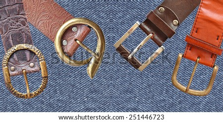 Belts with buckle unit on denim ( jeans) fabric texture background - stock photo