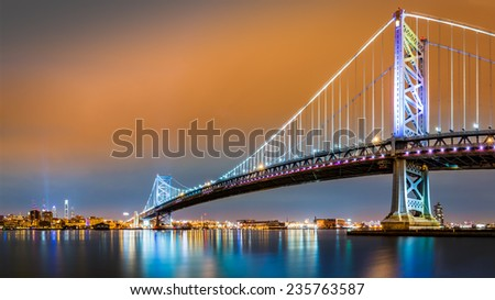 Ben Franklin Bridge and Philadelphia skyline by night as viewed from Camden across the Delaware river - stock photo