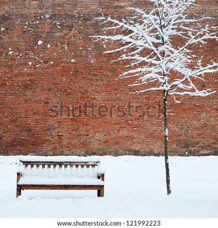 Bench and lonely tree covered by heavy snow - stock photo