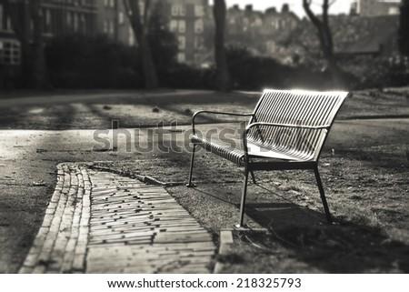 Bench in autumn park  - London, England Sepia color Shallow Focus - stock photo
