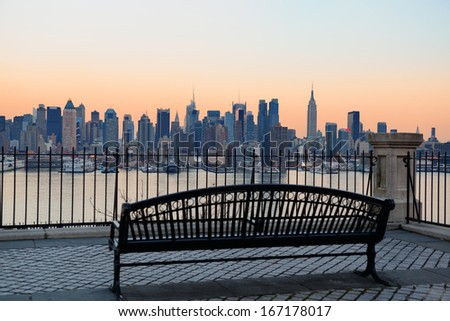 Bench in park and New York City midtown Manhattan at sunset with skyline panorama view over Hudson River - stock photo