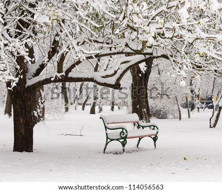bench in the park in the snow in winter - stock photo