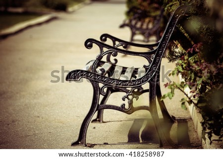 Bench in the park, vintage effect. Only the bench is in focus   - stock photo