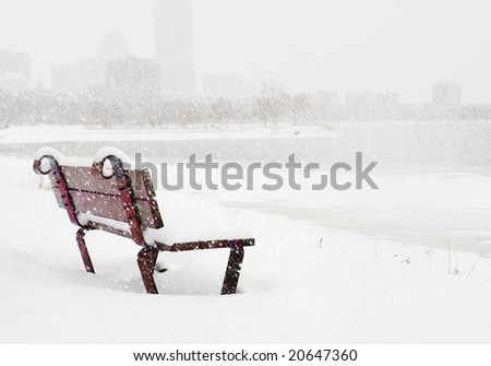 Bench in the snow on Charles River in Boston - stock photo