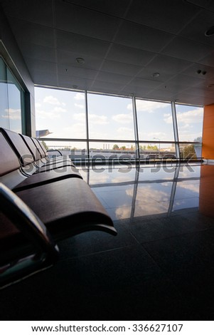 Bench in the terminal of airport. Empty airport terminal waiting area with chairs. - stock photo