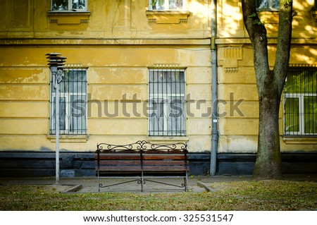 bench near old yellow house facade with street lamp - stock photo