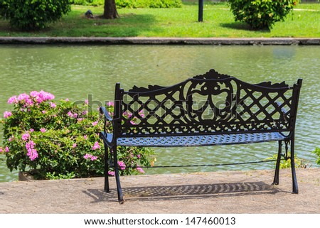 Bench near the Lake in the Tropical Garden - stock photo