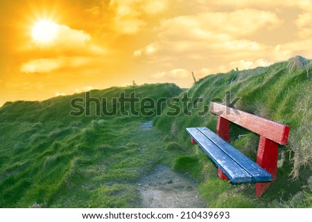 bench on a cliff edge  with views of Ballybunion beach and coast at sunset - stock photo