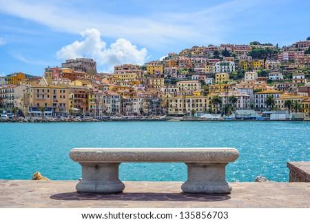 Bench on seafront in Porto Santo Stefano harbor, Monte Argentario, Tuscany, Italy. - stock photo