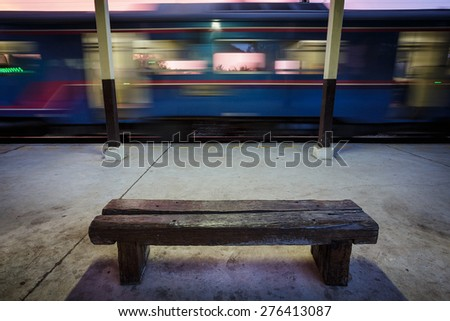 Bench on the platform with moving fast train - stock photo