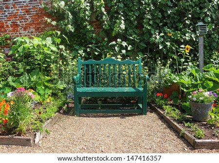 Bench seat surrounded with Summer Flowers in an english walled garden  - stock photo
