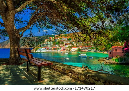 Bench under a tree on a sunny day at Assos beach, Kefalonia, Greece - stock photo