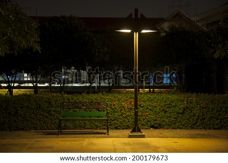 Bench under lamp In a park during the night. - stock photo