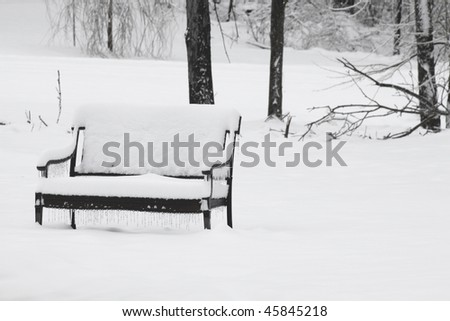 Bench under snow - stock photo