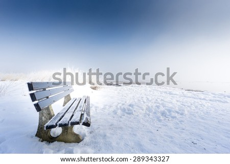 bench with ice on snowy winter day, lake chiemsee - stock photo