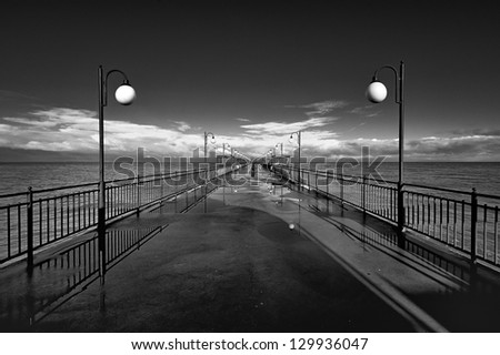 Benches and lamp posts on a pier - stock photo