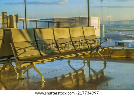 Benches at airport reflecting on marble floor in eartly sunlight - stock photo